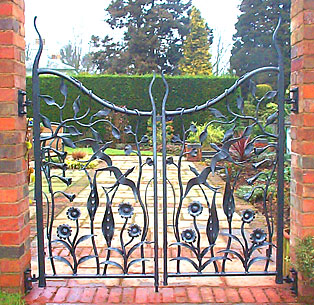 pair of garden gates with birds and flowers in forged metal