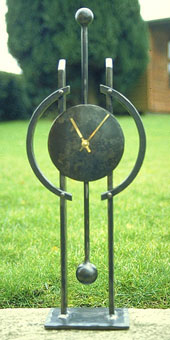 a mantlepiece clock in metal, a contemporary clock
